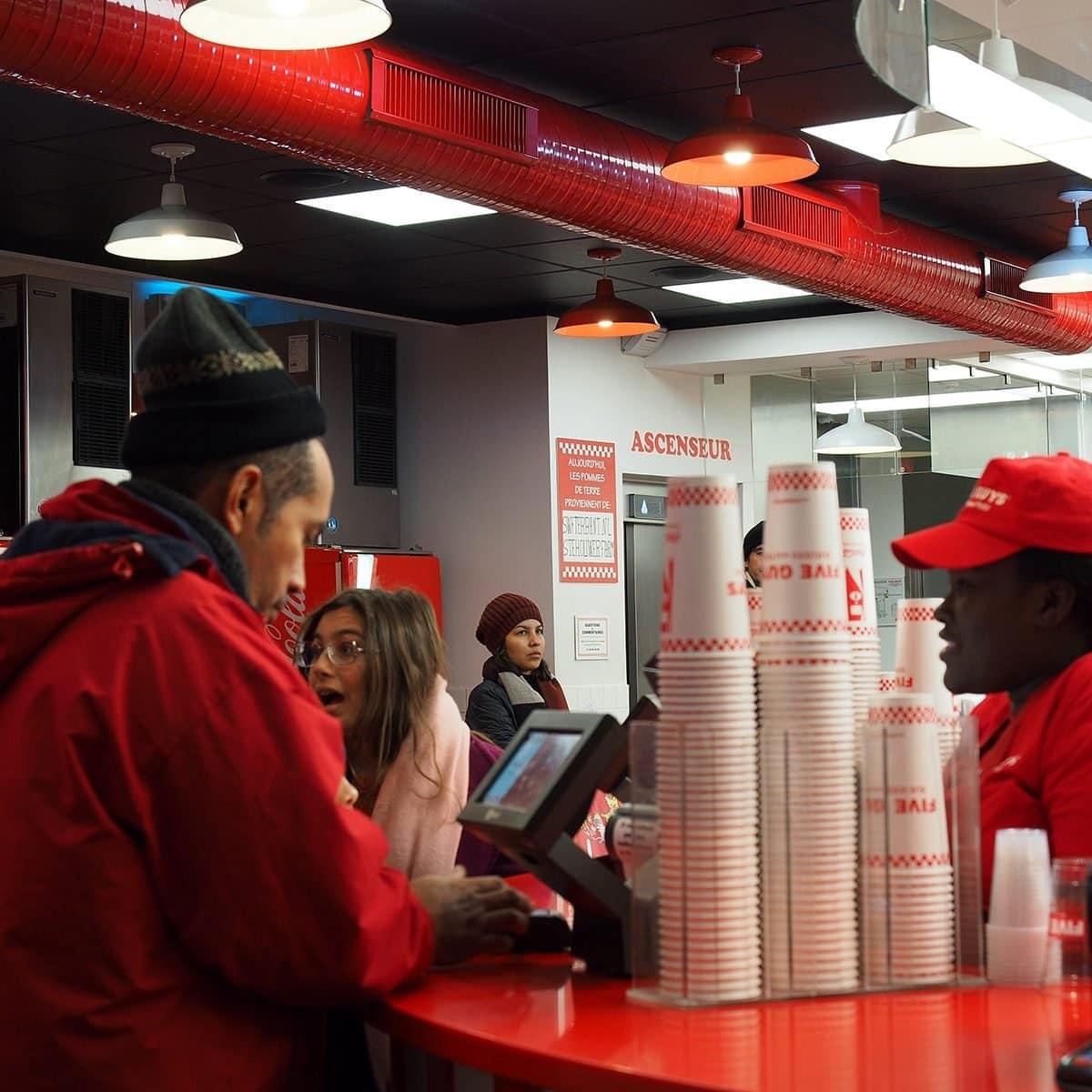 Primer plano de las tripulaciones que trabajan en la cadena de hamburguesas Five Guys, Avenue des Champs-Élysées, París, Francia