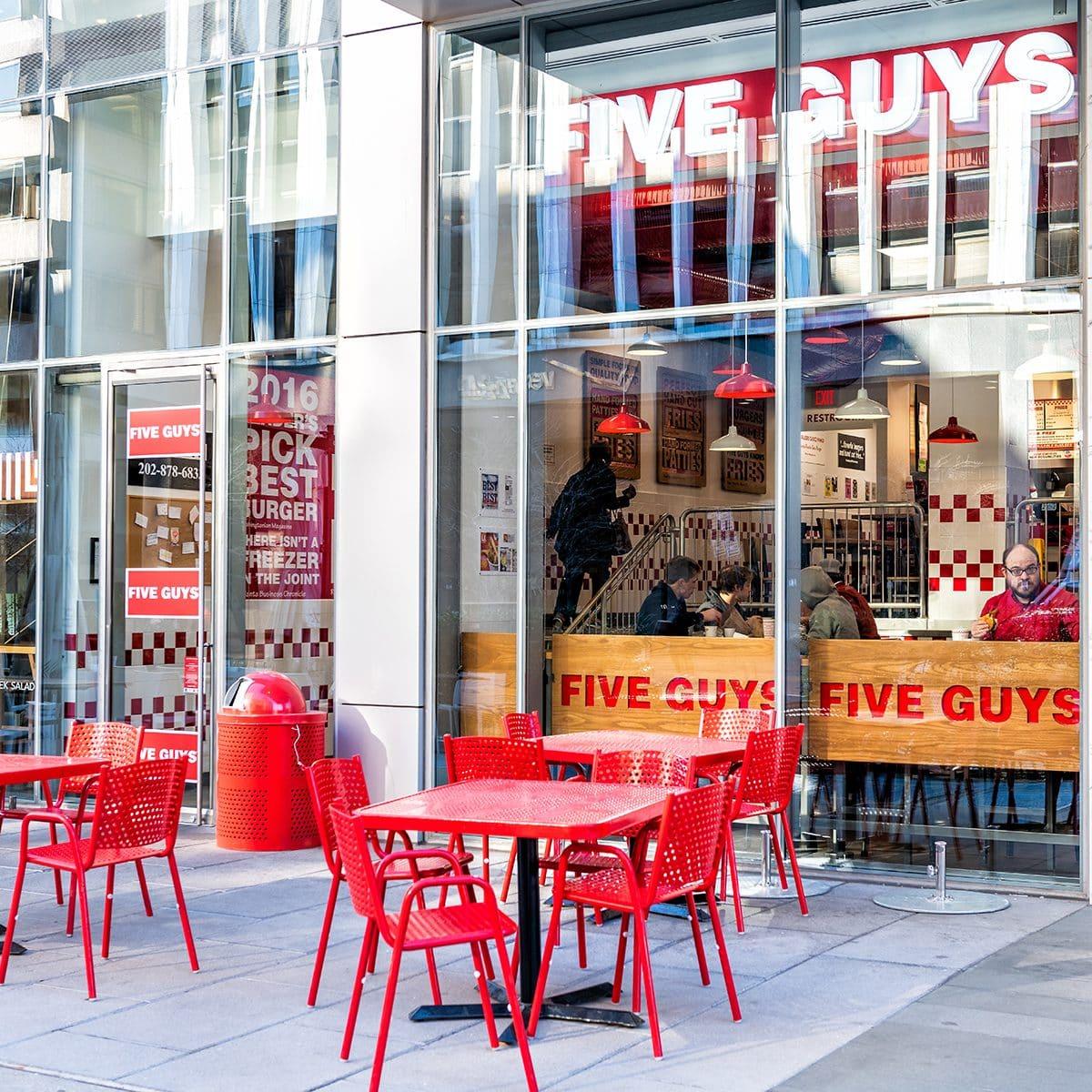 Restaurante Five Guys, entrada de la cadena de hamburguesas de la tienda en el Distrito de Columbia con sillas, mesas, exterior, zona de estar al aire libre, gente comiendo