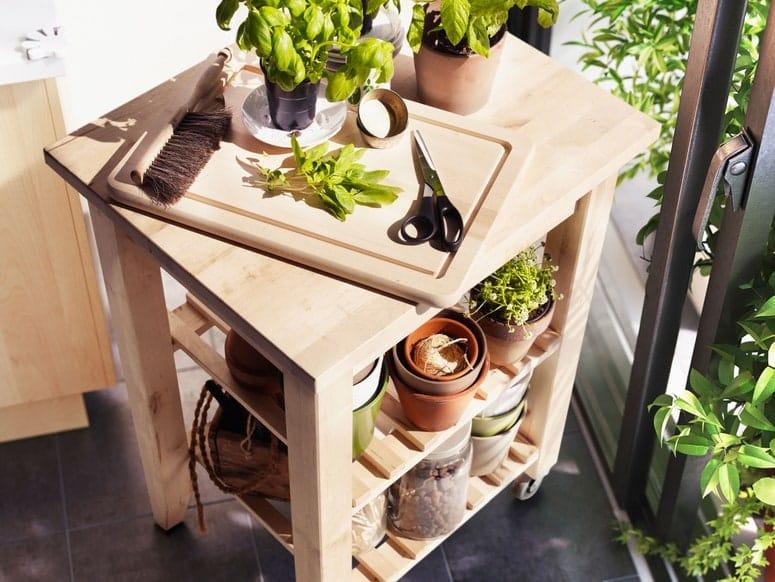 Foto de un carrito de cocina IKEA BEKVÄM con una olla de albahaca, tijeras y una tabla de cortar encima.