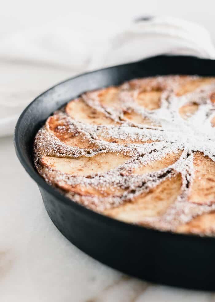 Primer plano de rodajas de manzana en un pastel de sartén de manzana cubierto con azúcar en polvo.