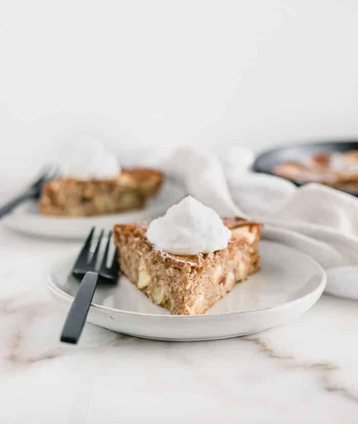 ¡Este pastel de sartén de manzana con especias es el postre perfecto para la transición al otoño!  Hecho con harina de trigo integral y un 50% menos de azúcar, ¡es lo suficientemente saludable como para desayunar!  |  AD #applecake #falldessert #lowsugar |  a través de livelytable.com