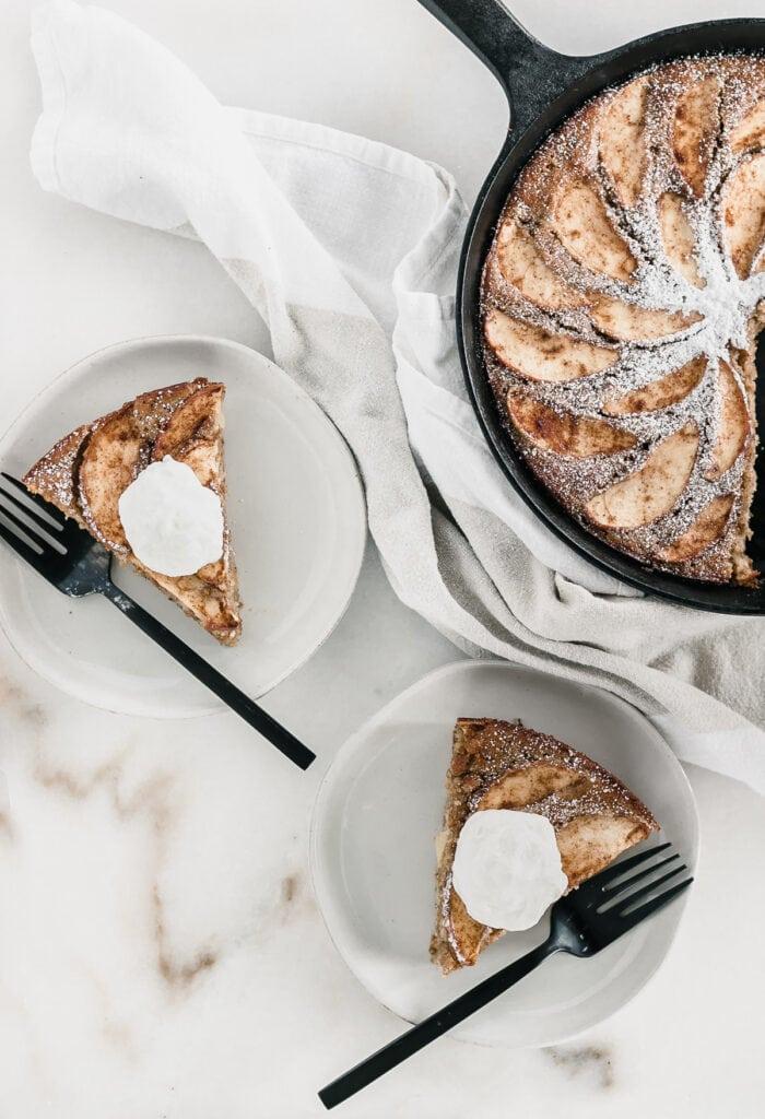 Vista aérea de dos platos con rebanadas de tarta de manzana cubiertas con crema batida y tenedores negros junto a tarta de manzana en una sartén.