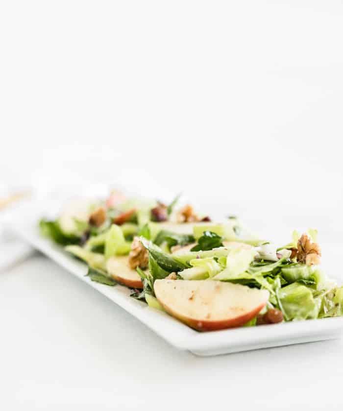 Ensalada de apio y manzana en un plato rectangular blanco.