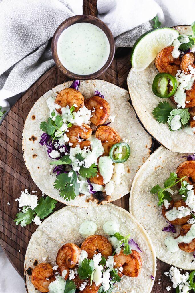 Tacos fáciles de camarones al chipotle con salsa de cilantro y jalapeño en una tabla de madera para servir.