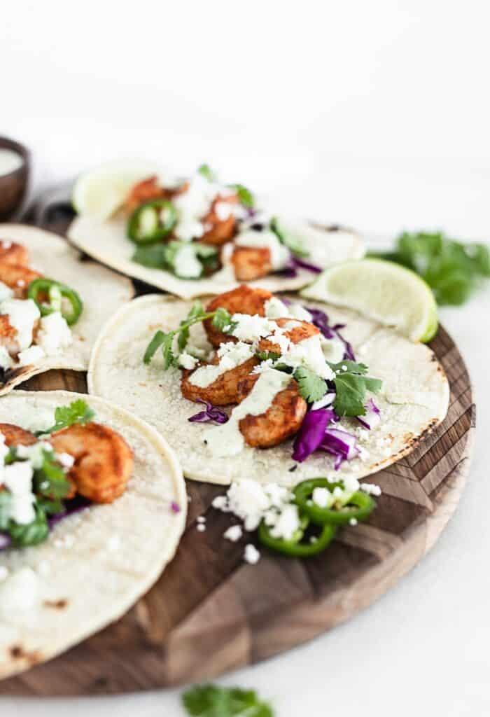 Cerca de tacos de camarones chipotle fáciles con salsa de cilantro y jalapeño en una bandeja de madera para servir.