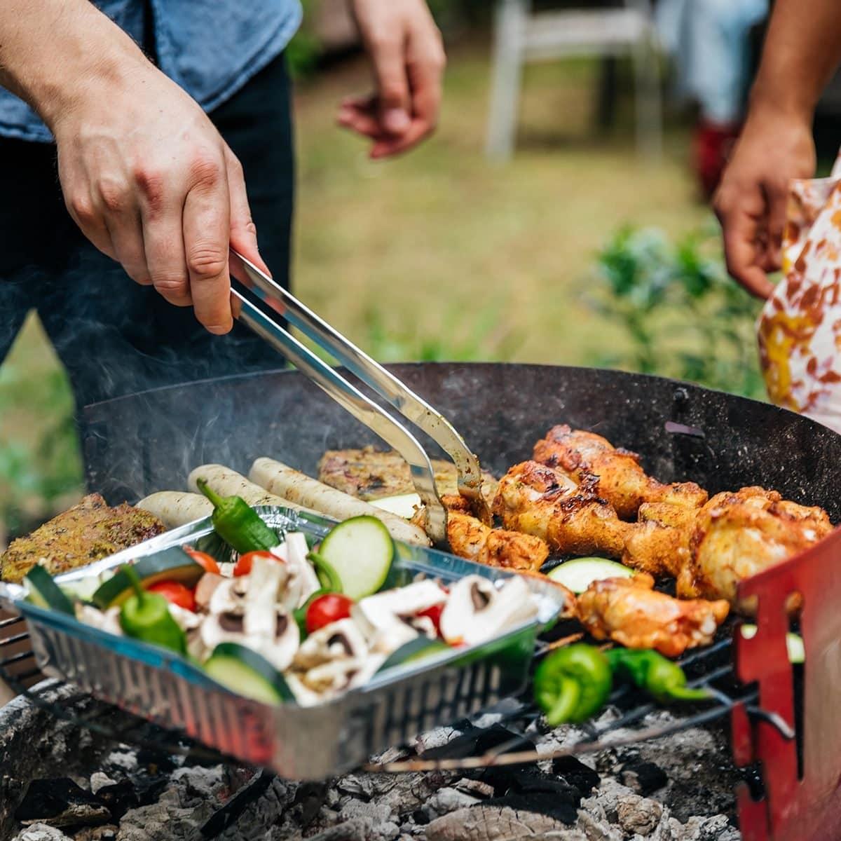 Un primer plano de aman cocinando diferentes alimentos en una barbacoa.