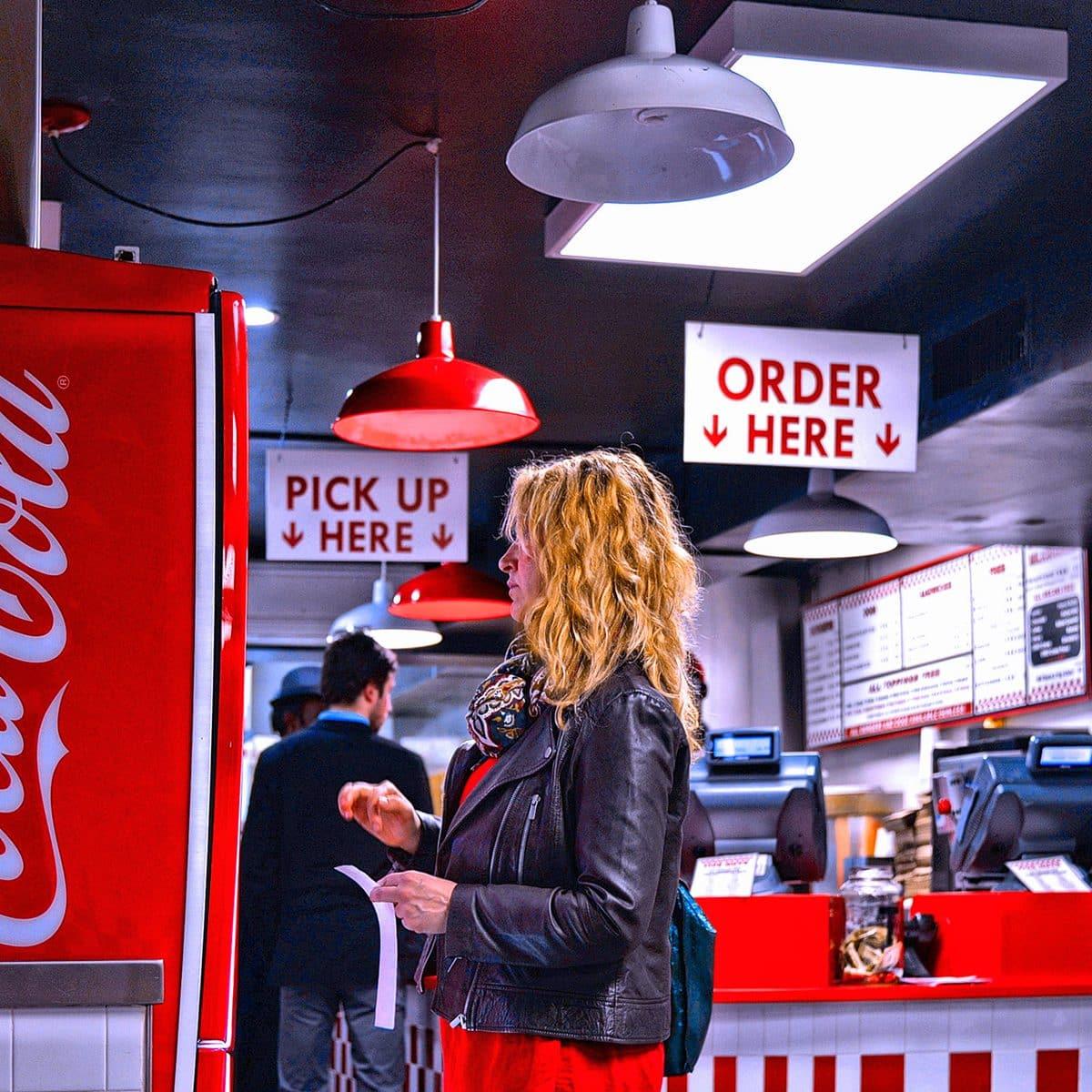 Gente comiendo en el restaurante de comida rápida Five Guys burger y una niña tomando una bebida de Coca Cola
