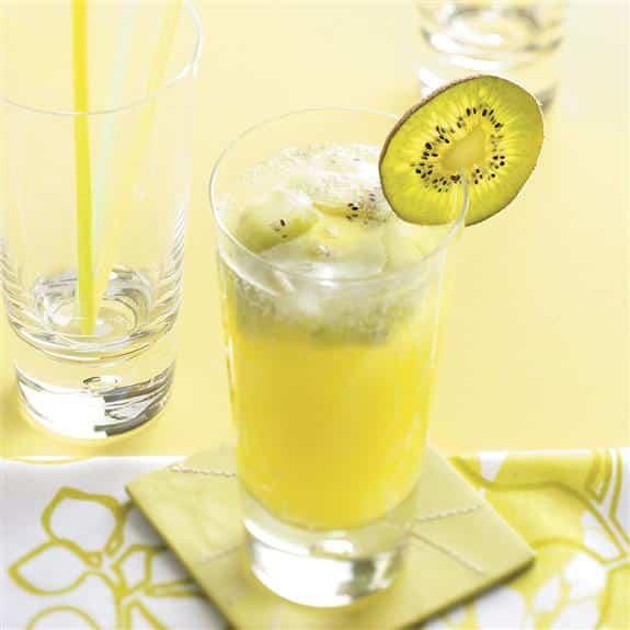 Limonada de kiwi espumoso en un vaso helado con una rodaja de kiwi como decoración en el borde