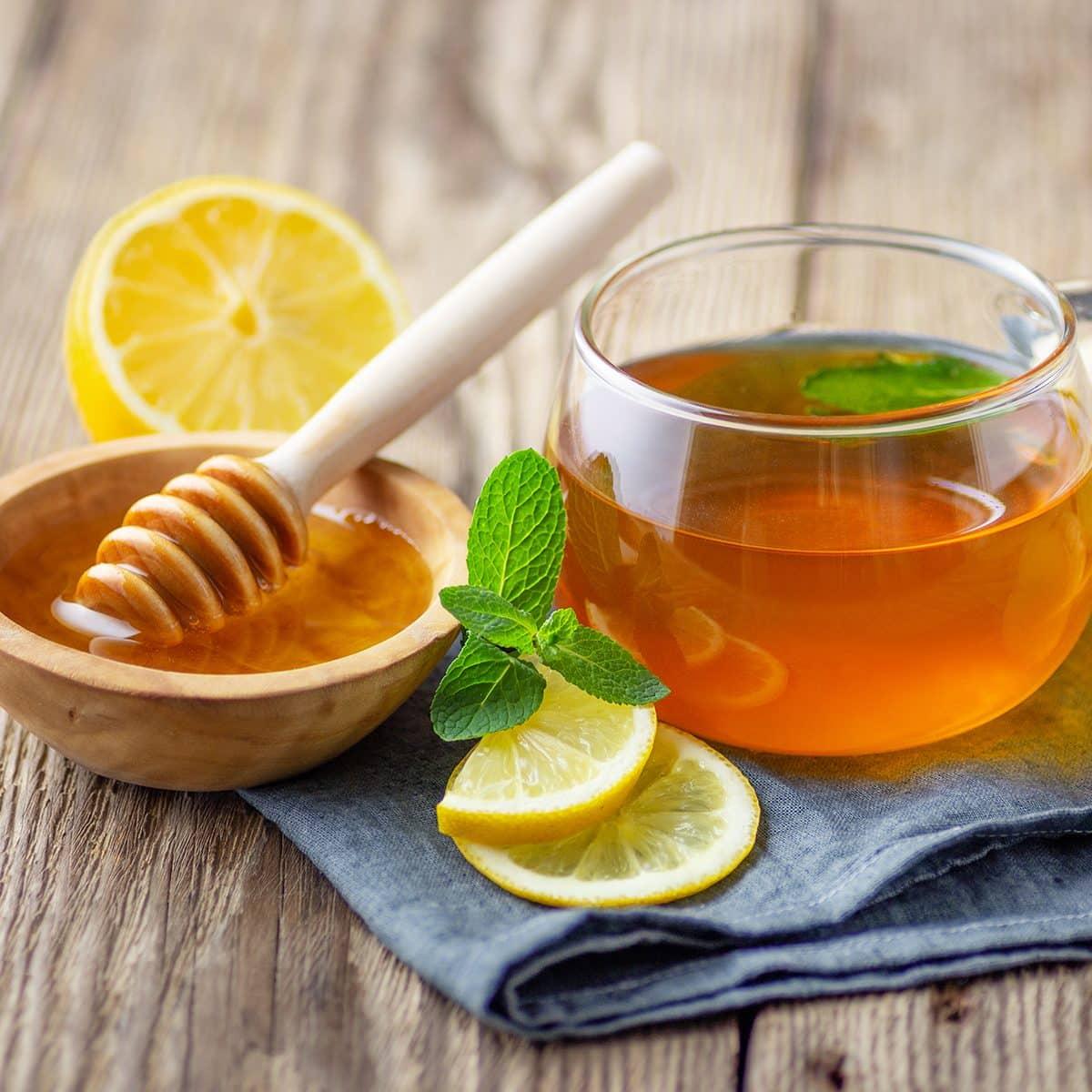 Una taza de té con limón, menta, jengibre y miel en la mesa rústica de madera.