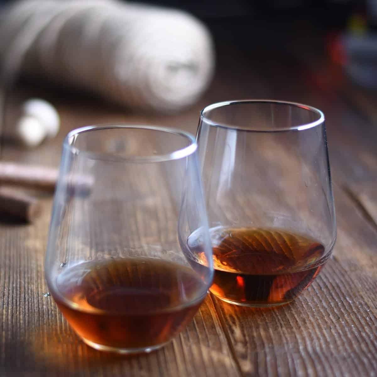 Vaso de ron en una mesa de madera rústica con puros y botella.