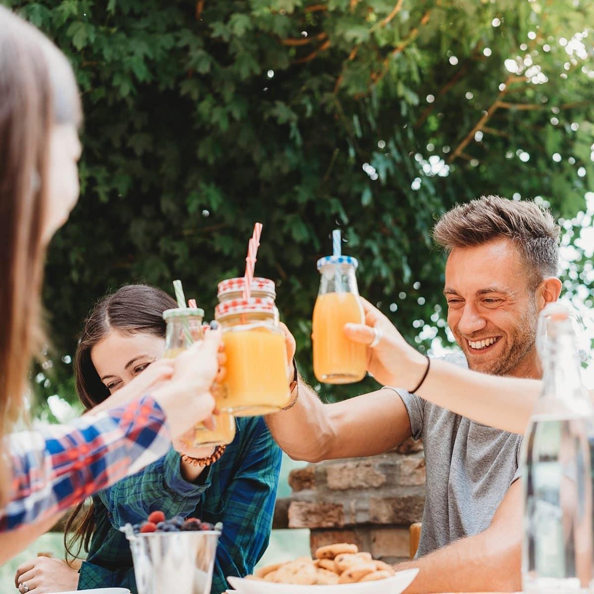 Grupo de amigos tomando un descanso en el campo juntos bebiendo jugos