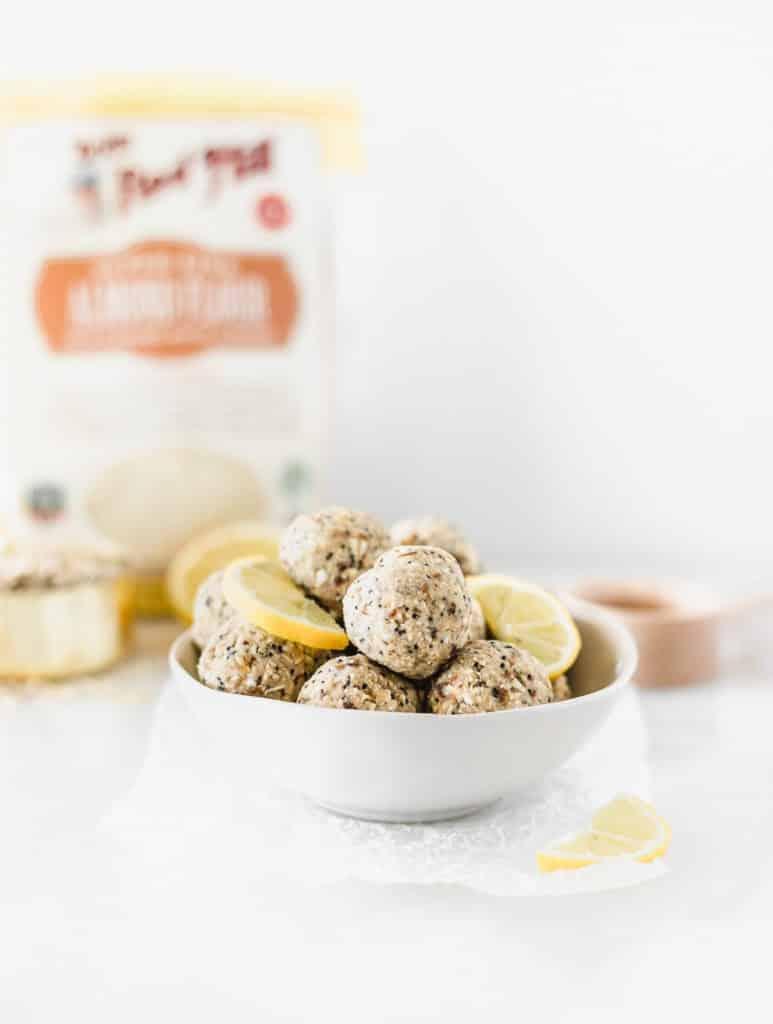 bolas de semillas de amapola de limón en un recipiente blanco con rodajas de limón, con harina de almendras y una taza medidora en el fondo.