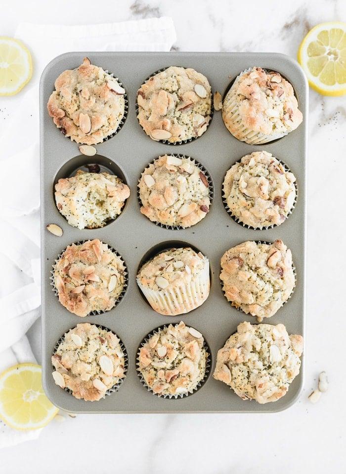 Vista aérea de muffins de limón con semillas de amapola en un molde para muffins rodeado de limones en rodajas.