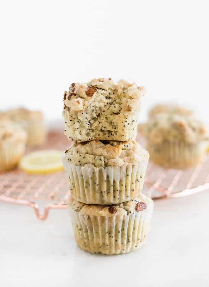 tres muffins de limón con semillas de amapola apilados uno encima del otro.  Al de arriba le han quitado un bocado.