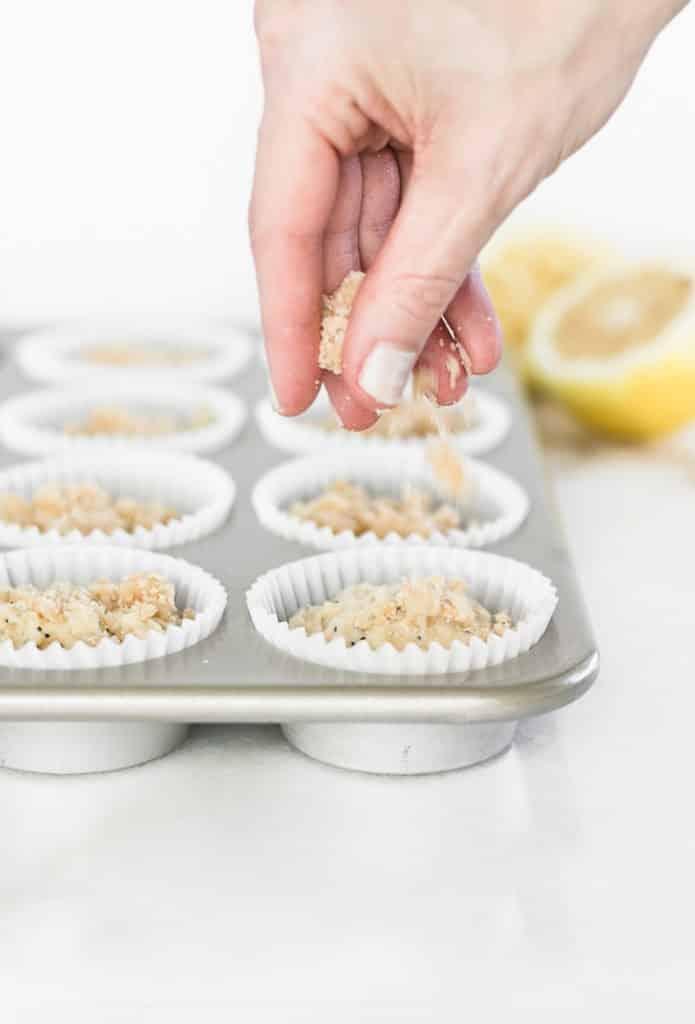 mano de streusel desmenuzado cubriendo la masa para muffins.