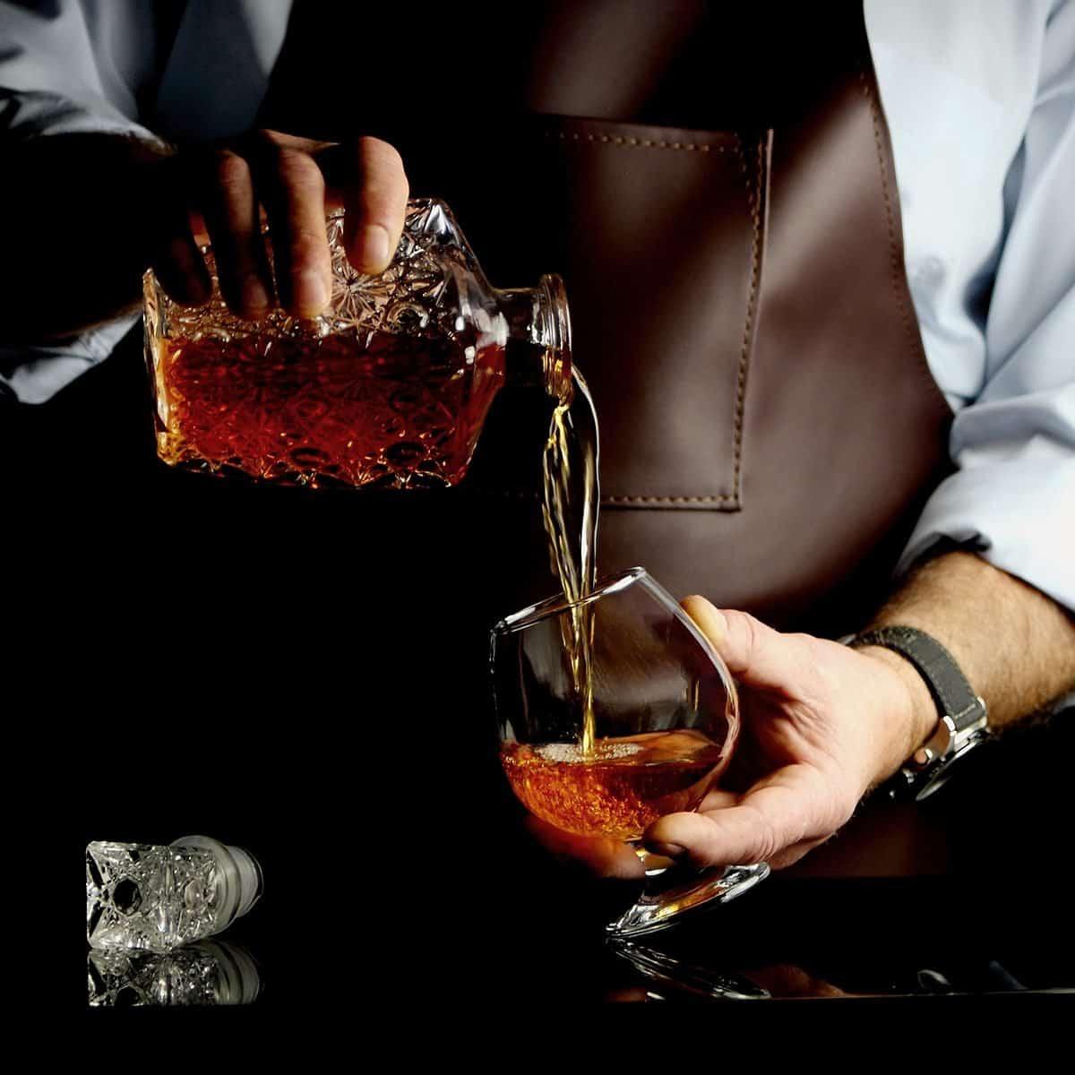 el hombre vierte brandy en un vaso detrás de la barra