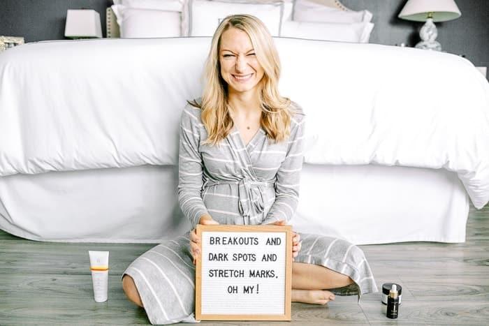 mujer sentada frente a una cama blanca con un letrero y productos para el cuidado de la piel