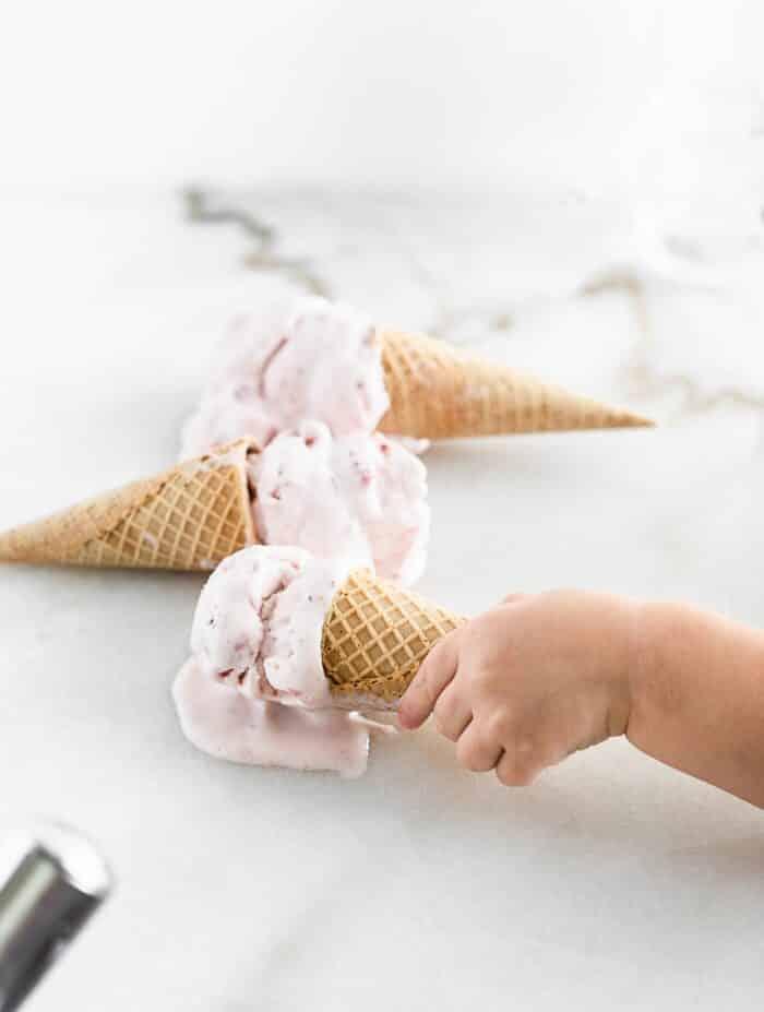 niño pequeño y agarrando un cono de helado de fresa de una superficie de mármol blanco con dos conos de helado en el fondo.