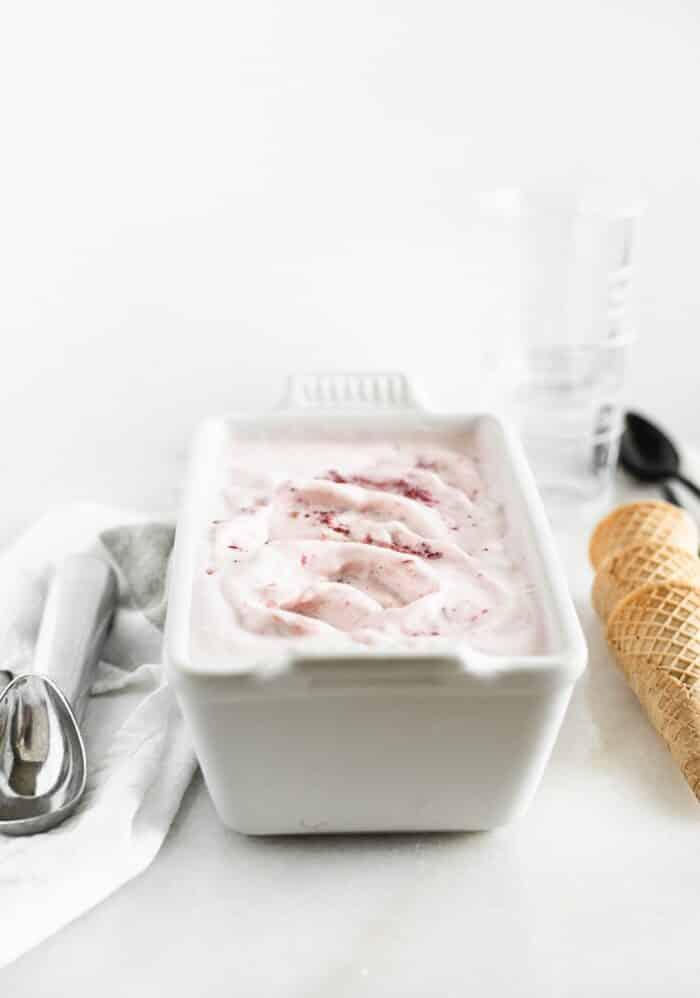 helado de fresa asado casero en un molde para pan blanco con una bola de helado y conos de helado a cada lado.