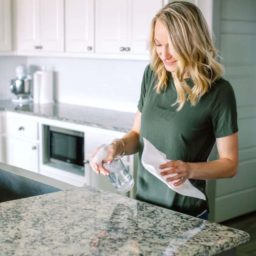 mujer con una camisa verde rociando la encimera de la cocina con una botella de spray de vidrio.
