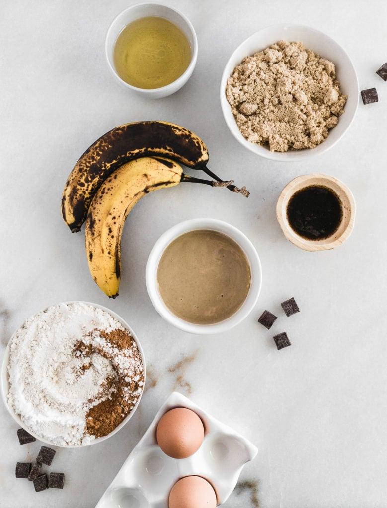 Vista aérea de los ingredientes para el pan de plátano tahini sobre un fondo blanco.