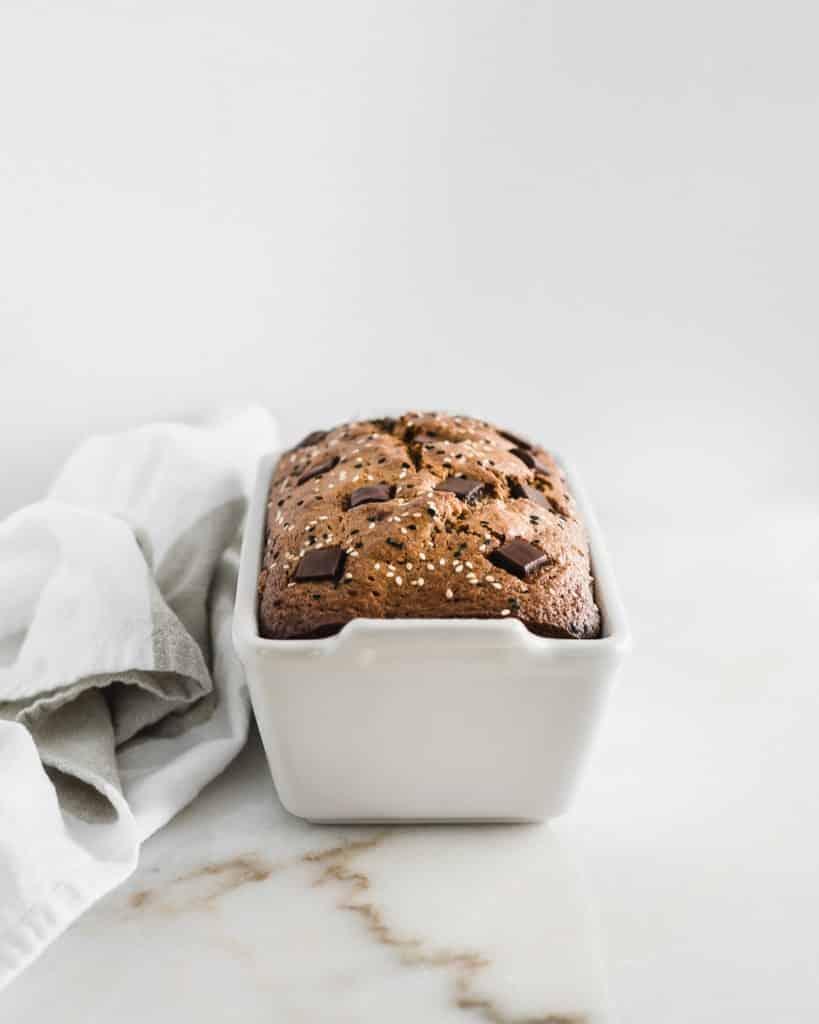 tahini pan de plátano con chispas de chocolate en un molde para pan blanco.