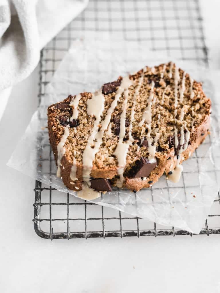 rebanada de pan de plátano con chispas de chocolate tahini en una rejilla de enfriamiento de metal rociado con tahini.