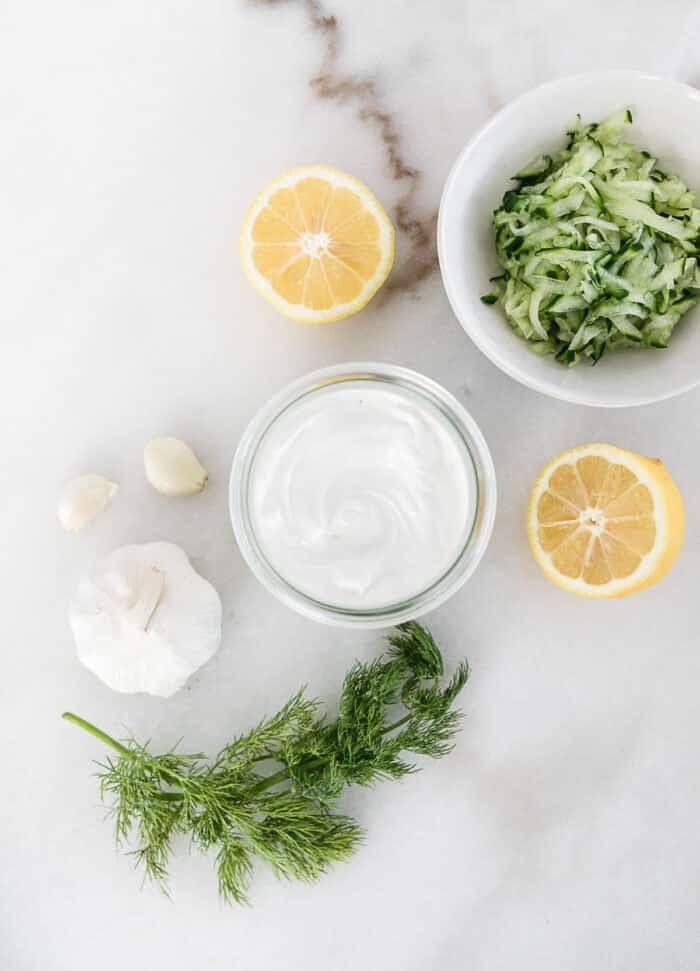 Vista aérea de los ingredientes para la salsa tzatziki sobre un fondo blanco.