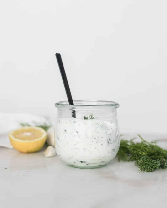 salsa tzatziki casera en un frasco de vidrio con una cuchara negra.