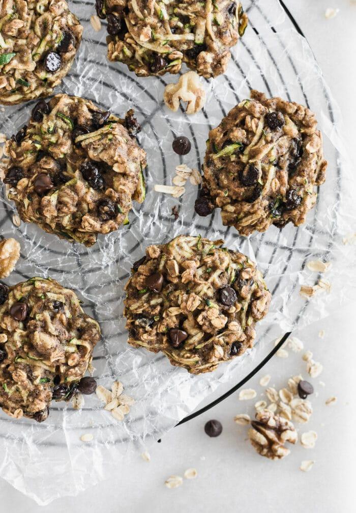 Vista aérea de galletas de desayuno de avena y calabacín en una rejilla de enfriamiento de alambre redondo.